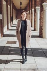 Stylish woman walking in an undercover corridor