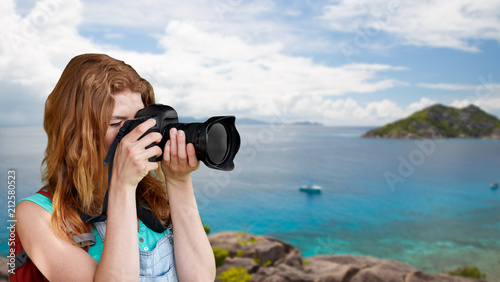 Leinwanddruck Bild travel, tourism and photography concept - happy young woman with backpack and camera photographing over background of seychelles island in indian ocean