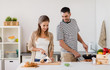 people and healthy eating concept - couple cooking food at home kitchen