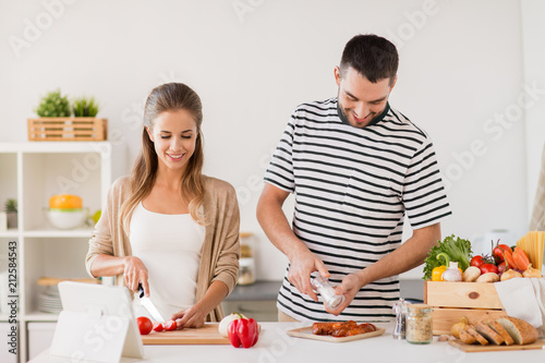 Wall mural people and healthy eating concept - happy couple cooking food at home kitchen