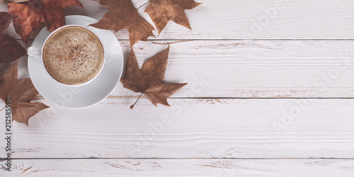 Plexiglas Herfst Hot coffee cappucino and autumn leaves on old white wooden background.Seasonal relax concept,flat lay