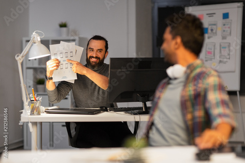 Leinwanddruck Bild business, deadline and web design people concept - happy creative man showing papers to colleague at night office
