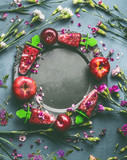 Round circle frame of homemade red berries fruits ice cream or Popsicle in plate on kitchen table background with garden flowers and ingredients, top view. Seasonal healthy organic still life - 212586709