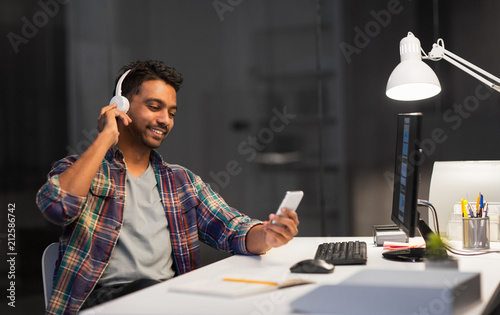 deadline, technology and people concept - happy creative man with headphones listening to music by smartphone and computer at night office - 212586742