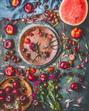 Various summer berries and fruits on rustic aged kitchen table with flowers and plates, top view, flat lay. Seasonal healthy local organic food and eating concept - 212588935