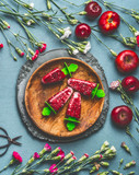 Wooden plate with homemade red fruits ice cream or Popsicle frozen fruit juice on rustic kitchen table background with garden flowers and ingredients, top view. Seasonal summer organic food still life - 212588961