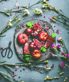 Plate with homemade red fruits ice cream or Popsicle frozen fruit juice on rustic kitchen table background with garden flowers and ingredients, top view. Seasonal summer organic food still life - 212588990