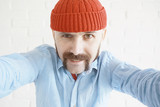 guy with a mustache in a red knitted hat - 212590594