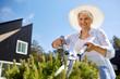 Leinwanddruck Bild - gardening, trimming and people concept - happy senior woman or gardener with hedge trimmer at summer garden