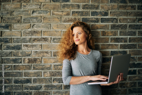 Fototapeta Portrait of woman holding laptop and standing in front of brick wall.