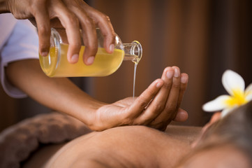 Therapist pouring massage oil at spa © Rido