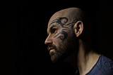tattoo on the face,  male portrait in the form of an assassin, cosplay,  tattooed brutal man,  guy with a tattooed face - 212593359