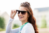 summer, eyewear and people concept - portrait of happy smiling young woman or teenage girl in sunglasses outdoors - 212593511