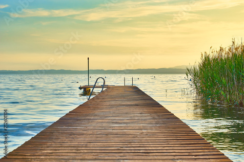Plexiglas Pier Long wooden pier at Lake Garda in Italy at sunset / slightley blurred picture with nice bokeh