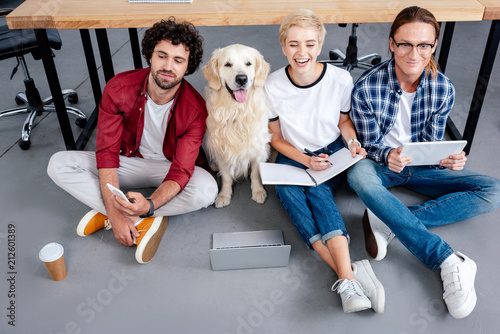 Leinwanddruck Bild high angle view of young startup team with labrador sitting on floor in office