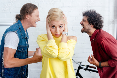 Wall mural young woman closing ears and looking at camera while male colleagues yelling behind