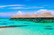 Quadro Luxury beach travel vacation concept: Overwater bungalows on turquoise coral reef lagoon ocean close to the beach.