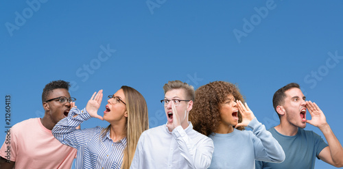 Leinwanddruck Bild Composition of group of friends over blue blackground shouting and screaming loud to side with hand on mouth. Communication concept.