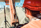 Worker on construction site operating wheel loader diligently  - 212607170