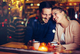 Romantic couple dating in pub at night - 212609720