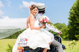 Wedding groom and bride driving motor scooter having fun, a just married sign attached  - 212611321