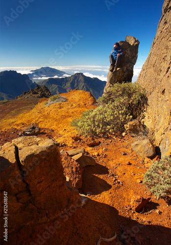 Fotobehang Bruin Resting man sitting on the rock above the crater Caldera de Taburiente, Island of La Palma, Canary Islands, Spain