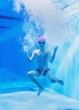 Leinwanddruck Bild - a little boy is having fun under water, tumbling and grimacing, making faces