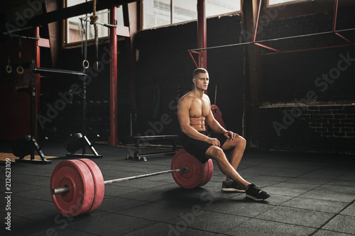 Sticker Muscular young man resting between sets