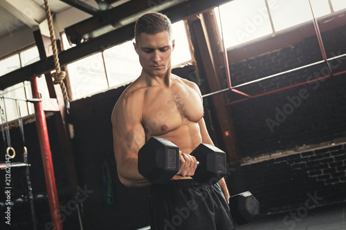Leinwanddruck Bild Young handsome bodybuilder during his arm workout in the gym