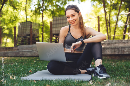 Portrait of a smiling young fitness girl using laptop - 212626168