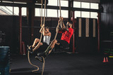 Two men doing rope climbing exercise - 212627198