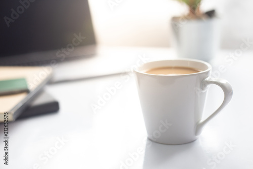 Coffee cup on notebook with laptop on white table in the morning sun light ,Working space