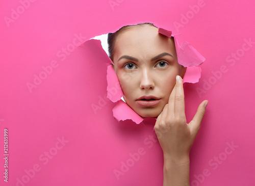 Beatiful girl looking through lacerated hole in stiff pink cardboard. Looking forward at camera. Having big blue eyes, perfecr eyebrow shape, pink plump lips. Tender, pretty. Posing in studio. - 212635999
