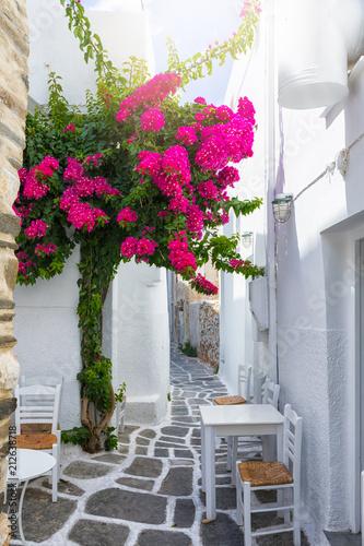 Kleine Gasse auf den Kykladen, Paros, Griechenland, mit weißen Häusern, Tischen und Stühlen und bunten Bougainvillea Blumen
