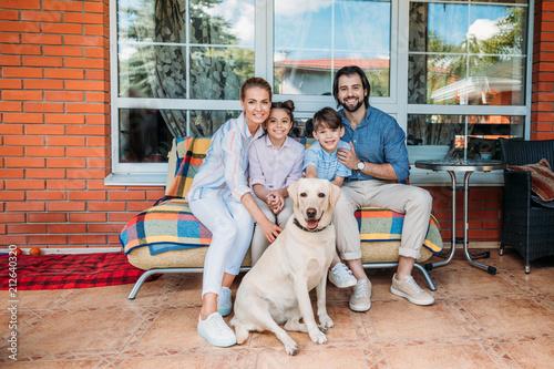 Leinwanddruck Bild smiling family labrador dog sitting on sofa together on country house porch