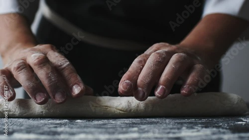 Wall mural Woman rolling the dough by hands, slow motion at 240 fps