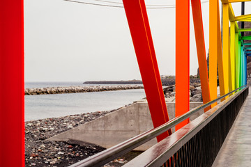 A contemporary brightly coloured metal rainbow truss bridge over a sea inlet in Tenerife. © HASPhotos
