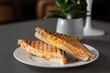 Halbierter Schinken Käse Toast mit Cheddar Käse und Kochschinken frisch und heiß getoastet im Kontaktgrill Presse, serviert in einem Restaurant  - 212646938