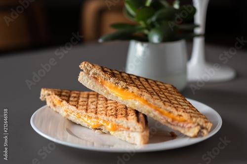 Poster Halbierter Schinken Käse Toast mit Cheddar Käse und Kochschinken frisch und heiß getoastet im Kontaktgrill Presse, serviert in einem Restaurant