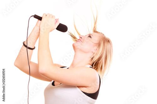 Fototapeta Blonde woman singing to microphone, profile view