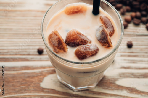 Poster Cold coffee glass with ice cubes on wooden table background. Ice coffee. Copy space.