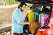 handsome man packing picnic basket at car trunk