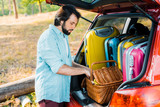 handsome man packing picnic basket at car trunk - 212659959