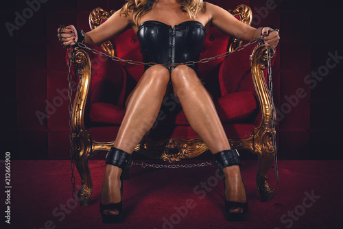 Leinwanddruck Bild Sensual provocation of a sexy bdsm woman on an armchair