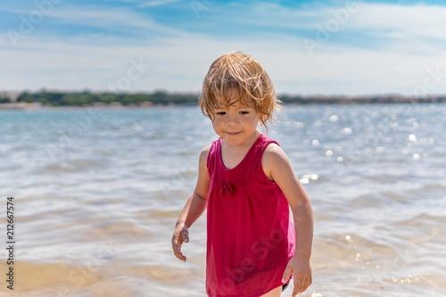 Foto Murales Little child girl on beach. Sea in background.