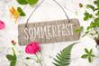 Leinwanddruck Bild - Sommerfest - Einladung / Karte mit Holzschild und verschiedenen Pflanzen (Erdbeerstaude, Rose, Farn, Geißblatt) auf einem rustikalen weißen Holz Hintergrund, top view