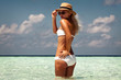 beautiful tanned woman on maldives island beach with turquoise sea on background