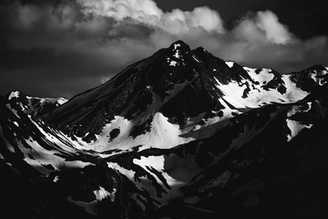 Beautiful nature landscape of snow mountains. Black and white monochrome toned. Telephoto zoom lens shot