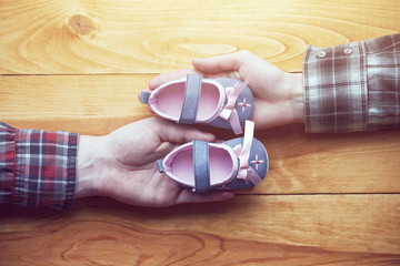 loving couple holding baby shoes with care and support