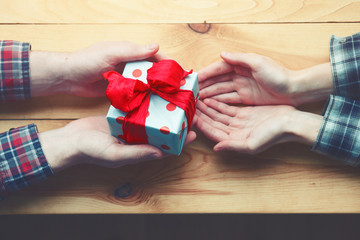 two hands of loving couple with gift box